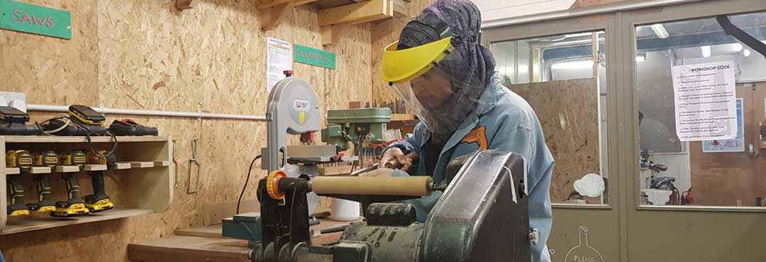 Woman working on a lathe as part of the Building Roots project