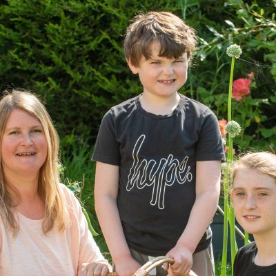 TCV volunteer Hayley with her children and their homegrown produce