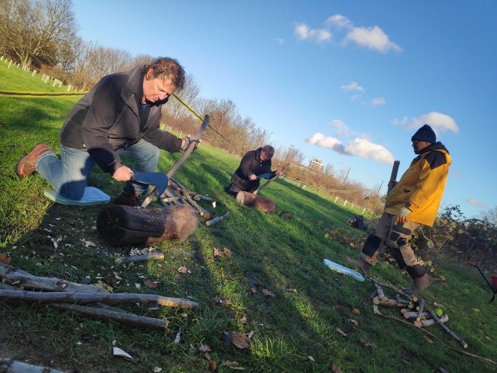Volunteers sharpening stakes using billhooks