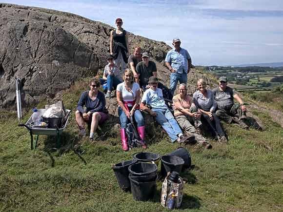 Volunteers taking a break on a hillside logo